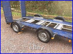 Twin spread axle car transporting trailer